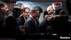 Babar Khan Ghori (R) of the Pakistan's political party Muttahida Qaumi Movement (MQM) hugs cleric and leader of Minhaj-ul-Quran Muhammad Tahirul Qadri after they reached an agreement on the fourth day of protests in Islamabad, January 17, 2013.
