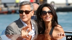 George Clooney, left, and Amal Alamuddin arrive in Venice, Italy, Sept. 26, 2014.