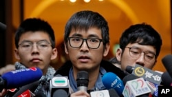 Pro-democracy activist Alex Chow, center, speaks to reporters outside the Court of Final Appeal in Hong Kong, Feb. 6, 2018. Hong Kong's highest court Tuesday overturned prison sentences for three young pro-democracy activists convicted for their roles in