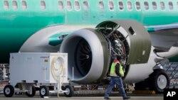 ພະນັກງານຄົນນຶ່ງ ຍ່າງຜ່ານ ເຄື່ອງຈັກໂບອິ້ງ 737 ຮຸ້ນແມັກສ໌ 8 ທີ່ສ້າງໂດຍໂບອິ້ງ ຢູ່ເມືອງເຣັນຕັນ ລັດວໍຊິງຕັນ (13 ມີນາ 2019)