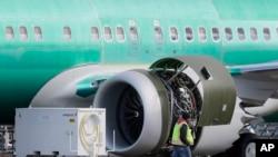 Seorang pekerja melintas mesin sebuah Boeing 737 MAX 8 yang tengah diproduksi untuk maskapai American Airlines di fasilitas perakitan milik Boeing Co. di Renton, Washington, 13 Maret 2019 (foto: AP Photo/Ted S. Warren)