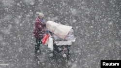 A woman pushing a stroller walks in the snow in Yantai, Shandong province, China December 4, 2017.