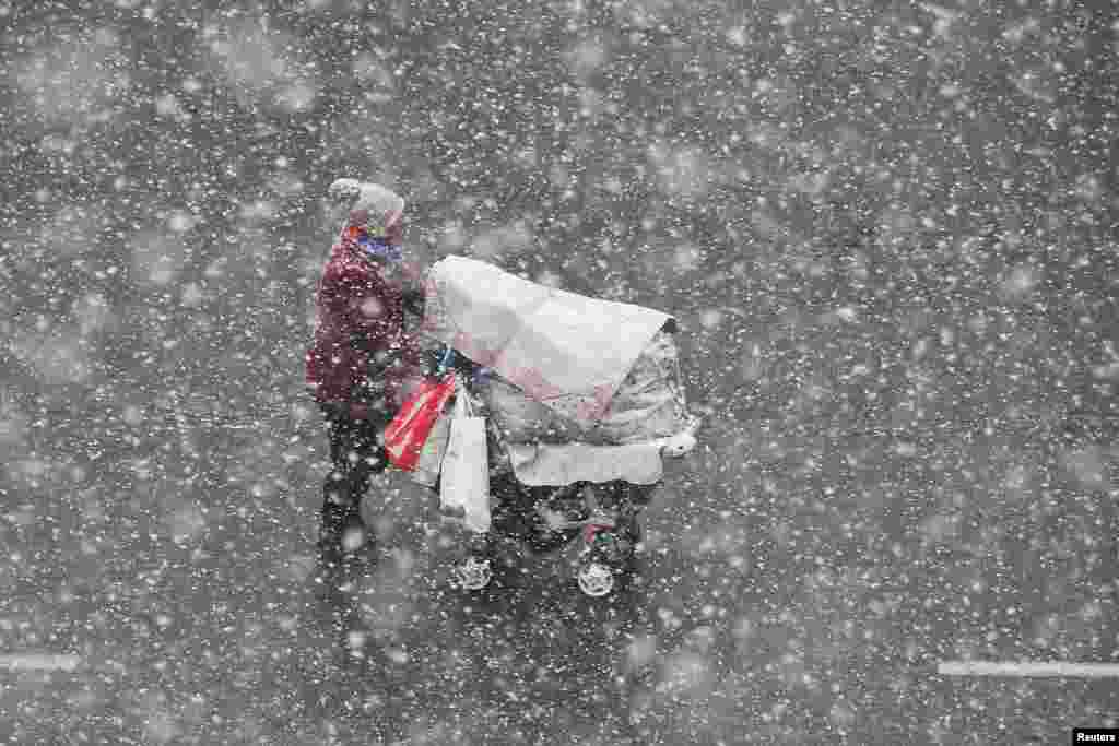 A woman pushing a stroller walks in the snow in Yantai, Shandong province, China.