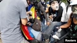 معترضان ونزوئلایی به جوانی که در جریان سرکوب پلیس جراحت مرگبار برداشته، کمک می کنند.