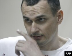 FILE - Ukrainian film director Oleg Sentsov looks out from a defendants' cage as he listens to the verdict at a military court in the southern city of Rostov-on-Don, Aug. 25, 2015.