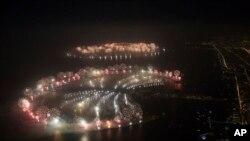 """Pesta kembang api di Pulau Palm Jumeirah (depan) dan World Islands (belakang), Dubai, dalam perayaan Menyambut Tahun Baru 2014 untuk memecahkan rekor """"Kembang Api Terpanjang"""" Guinness World Record (1/1)."""