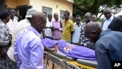 Relatives and onlookers watch as the body of South Sudanese journalist Moi Peter Julius is taken into a mortuary in Juba, South Sudan, Aug. 20, 2015.