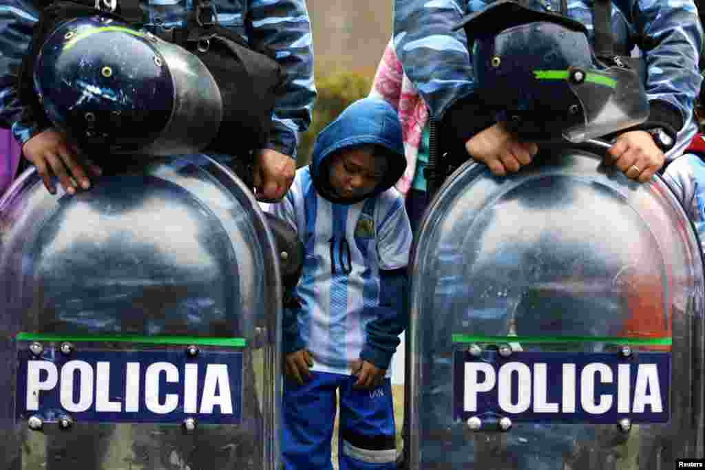 An Argentine fan stands between policemen as they gather to welcome their team outside the Argentine Football Association (AFA) in Buenos Aires after Argentina lost to Germany in their 2014 World Cup final soccer match.