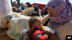 Người Syria tỵ nạn cho con uống sữa tại một cửa khẩu biên giới gần Suruc, Thổ Nhĩ Kỳ.