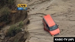 This image taken from video provided by KABC-TV, shows a vehicle stuck along a muddy road in the mountainous community of Green Valley, Calif., about 65 miles northwest of downtown Los Angeles, Oct. 15, 2015.