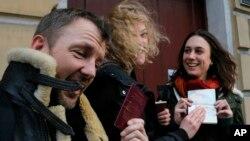 """Atrof-muhit himoya uchun kurashuvchi """"Greenpeace"""" tashkiloti faollari, britaniyalik Filipp Boll, finlyandiyalik Sini Saarela va britaniyalik Aleksandra Xarris Rossiyadan ketishga ruxsat olganidan xursand. Sankt-Peterburg, 26-dekabr, 2013-yil."""