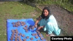 A briquette producer trained by Legacy Foundation instructors displays her wares (Photo: Legacy Foundation)