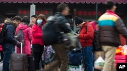 Passengers carry their belongings while arriving at the Beijing railway station in Beijing, Jan. 19, 2014.