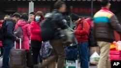在北京火車站旅客們拉著行李戴著口罩抵達。