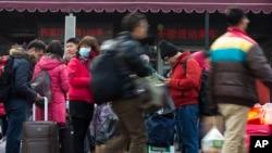 旅客们拉着行李戴着口罩抵达北京火车站。(2014年1月19日)