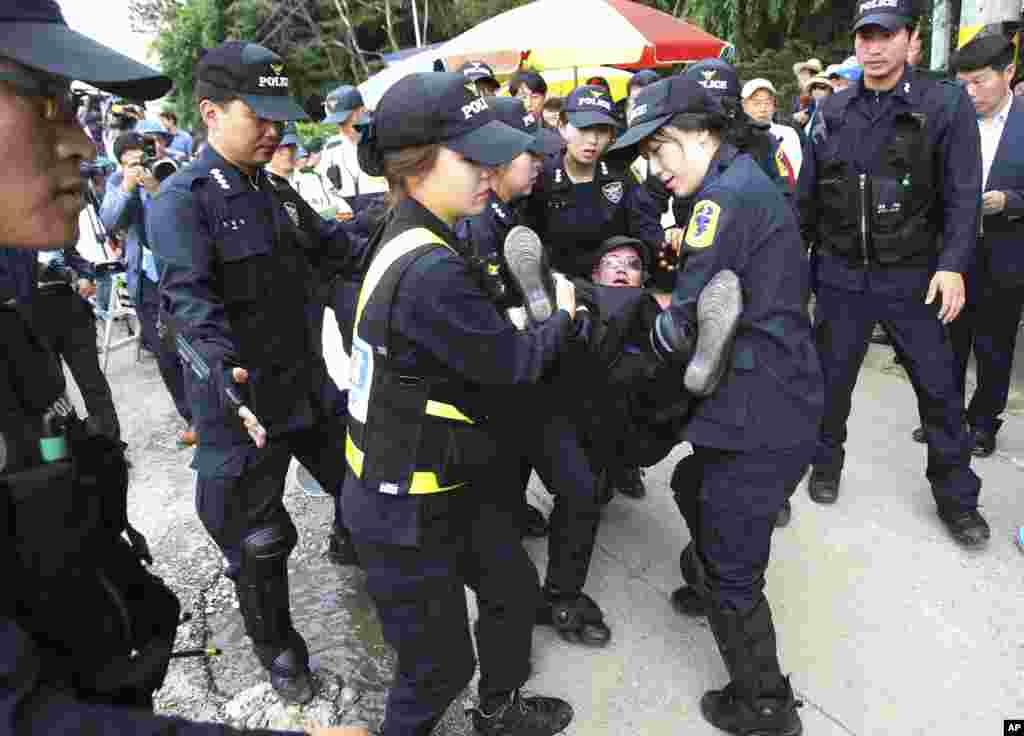 Police officers separate a Buddhist believer from Evangelical Baptist Church believers as she denounced them near the main gate of the church in Anseong, South Korea, Wednesday, June 11, 2014.