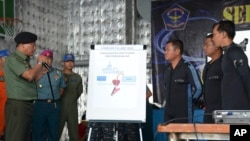 Indonesian military chief Gen. Moeldoko, left, briefs navy divers onboard the navy vessel KRI Banda Aceh in an area where they found the tail of AirAsia Flight 8501 on the Java Sea, Indonesia, Jan. 8, 2015.