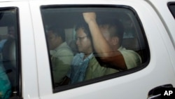 Ny Chakrya, center, former ADHOC and a National Election Committee member who worked at the organization, sits in a car and is transported back to an Anti-Corruption Unit, ACU, after a short appearance at Phnom Penh Municipal Court, in Phnom Penh, Cambodia, Saturday, April 30, 2016. Cambodian authorities arrested five human rights workers last Friday on accusations they tried to help cover up a woman's affair with the deputy leader of the opposition Cambodia National Rescue Party. The action is the latest in a series by Prime Minister Hun Sen's government putting legal pressure on its critics and political opponents. (AP Photo/Heng Sinith)