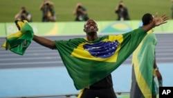 Usain Bolt de la Jamaïque bras étendus, couvert du drapeau brésilien et tenant le drapeau de son pays en main, célèbre après avoir remporté la médaille d'or en finale du 4x100 mètres relais messieurs lors des compétitions d'athlétisme des Jeux Olympiques d'été de 2016 au stade olympique de Rio de Janeiro, au Brésil, 19 août 2016.