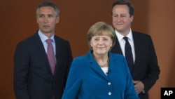 German Chancellor Angela Merkel, center, British PM David Cameron, right, and Norway's PM Jens Stoltenberg, left, arrive for a panel discussion in Berlin, Germany, June 7, 2012.