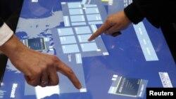 在汉诺威微软电脑展上工作人员使用云计算软件触摸屏