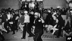 FILE - In this Aug. 29, 1968, file photo, Chicago Police attempt to disperse demonstrators outside the Conrad Hilton, the downtown headquarters for the Democratic National Convention in Chicago.
