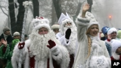People dressed as Father Frost, the named used locally for Santa Claus, and Snow Maiden greet passers-by during a New Year parade in Bishkek, Kyrgyzstan. (Reuters Image)