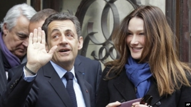 French President and UMP candidate Nicolas Sarkozy and his wife Carla Bruni-Sarkozy leave after casting their votes in the first round of French presidential elections in Paris, France, Sunday, April 22, 2012.