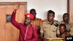 Opposition figurehead Robert Kyagulanyi, aka Bobi Wine, lifts his hand in the dock in the court room in Kampala, April 29, 2019.