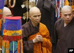 In this file photo, Vietnamese Zen master Thich Nhat Hanh, center, arrives for a ceremony in Ho Chi Minh City in Vietnam. Vietnam's communist government has had difficult dealings with religious freedom.