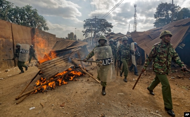 Riot police walk past burning barricades erected by protesters throwing rocks, during clashes in the Kawangware slum of Nairobi, Kenya, Aug. 10, 2017.