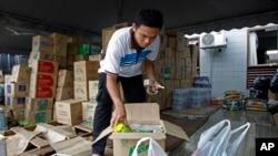 Seorang sukarelawan dari Muslim Care Malaysia Society mengepak mie instan di sebuah kotak untuk dikirimkan ke daerah yang dilanda banjir di wilayah timur, di Shah Alam, di luar Kuala Lumpur, Malaysia, Sabtu, 27 Desember 2014. Perdana Menteri Malaysia Najib Razak mengatakan pada hari Jumat ia mempersingkat liburannya di AS untuk memimpin upaya penanggulangan banjir terburuk di negara tersebut yang telah menewaskan lima orang dan menyebabkan lebih dari 100.000 orang mengungsi. (AP Photo/Lai Seng Sin)