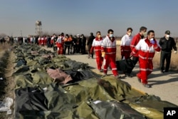 Rescue workers carry the body of a victim of a Ukrainian plane crash in Shahedshahr, southwest of the capital Tehran, Iran, Wednesday, Jan. 8, 2020.