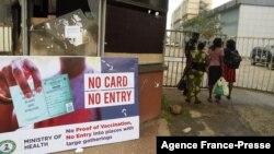 나이지리아 남부의 시설 경비 요원이 출입자들의 신종 코로나바이러스 백신 접종 카드를 확인하고 있다.