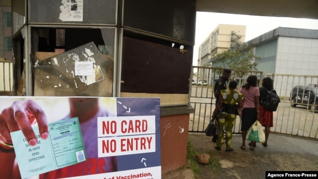 A security official examine workers COVID-19 vaccination passes in Benin City capital of Edo State, southern Nigeria, on Sept. 16, 2021.