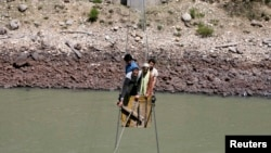 People cross the Chenab river on a trolley tied to wires to cast their vote at Harshi village in Doda district, north of Jammu, India April 17, 2014.