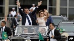 Diapit oleh Ibu Negara Michelle Bolsonaro, Presiden Brazil Jair Bolsonaro melambaikan tangan saat mengendarai mobil terbuka setelah upacara pelantikan di Brasilia, Brazil, 1 Januari 2018.