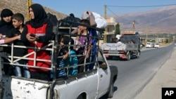 Người dân Li Băng ở phía sau của một chiếc xe tải nhỏ chạy lánh nạn khỏi thị trấn Arsal gần biên giới Syria, ngày 4/8/2014.