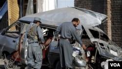 Polisi Afghanistan menginspeksi bangkai bus mini yang dihancurkan bom di Jalalabad, provinsi Nangarhar, Kamis (21/4).
