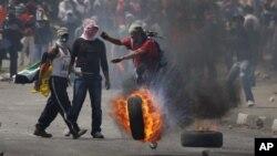 Palestinos lanzan un neumático incendiado contra tropas israelíes cerca de Ramala, en Cisjordania.