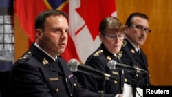 From left, James Malizia and Jennifer Strachan, both Royal Canadian Mounted Police officials, and Deputy Commissioner Scott Tod of the Ontario Provincial Police talk to reporters in Ottawa after announcing terror-related charges against three men, Feb. 3, 2015.