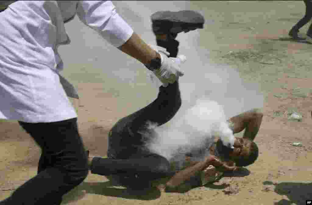 Palestinian medic rushes to a a protester who got shot in his mouth by teargas canister fired by Israeli troops near the Gaza Strip's border with Israel, east of Khan Younis, in the Gaza Strip.