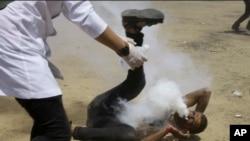 Petugas medis Palestina bergegas menolong seorang pengunjuk rasa yang terkena tabung gas air mata di mulutnya yang ditembakan oleh tentara Israel, di timur Khan Younis, Jalur Gaza, Jumat, 8 Juni 2018.