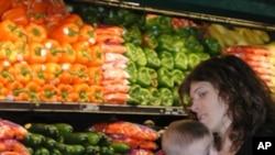 带着婴儿的妇女在商店挑选蔬菜