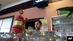 A bar tender pours beer for customers in Phnom Penh, Cambodia, file photo.