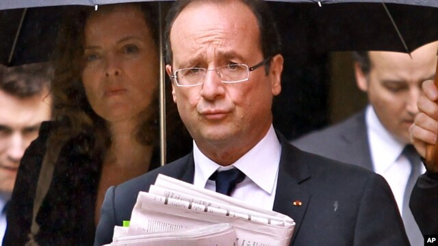 French President Francois Hollande holds newspapers accompanied by his companion Valerie Trierweiler, left, in Tulle, June 10, 2012.