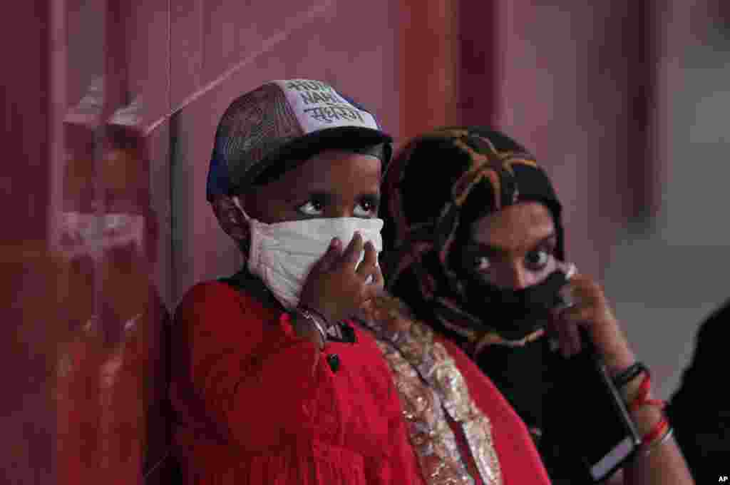 A woman and a child wait to give their nasal swab samples to test for COVID-19 at a government hospital in Unchahar, Raebareli district, Uttar Pradesh, India, Monday, Sept. 28, 2020. (AP)