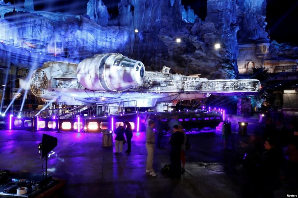 """Гости исследуют выставку """"Звездные войны: край галактики"""", рядом со звездолетом Millennium Falcon, в Диснейленд-парке в Анахайме, Калифорния, 29 мая 2019 года."""