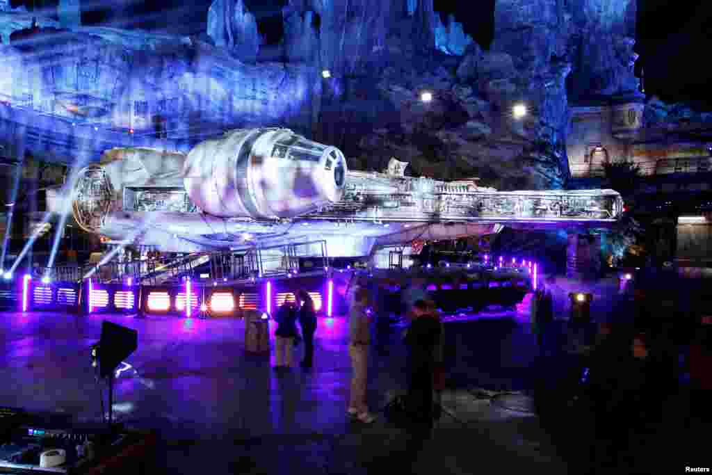 "Guests explore the ""Star Wars: Galaxy's Edge"" exhibit, near a Millennium Falcon starship, at Disneyland Park in Anaheim, California, May 29, 2019."