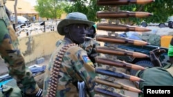 FILE - A South Sudanese army soldier stands next to a machine gun mounted on a truck in Malakal town, some 500 km (312 miles) northeast of the capital, Juba.